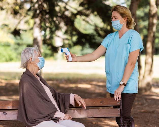 Verpleegkundige die de temperatuur van de senior vrouw buiten op een bankje controleert Gratis Foto