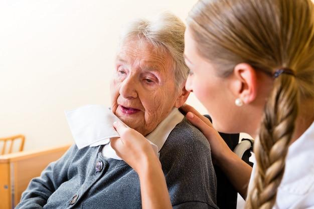 Verpleegster afvegende mond van hogere vrouw in verpleeghuis Premium Foto