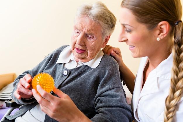 Verpleegster die fysieke therapie geeft aan hogere vrouw Premium Foto
