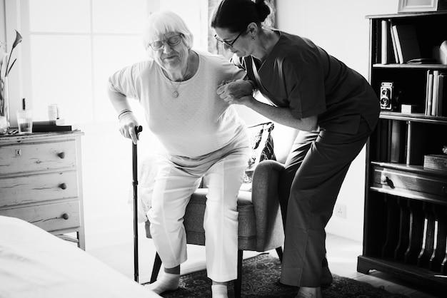 Verpleegster die hogere vrouw helpen om zich te bevinden Gratis Foto