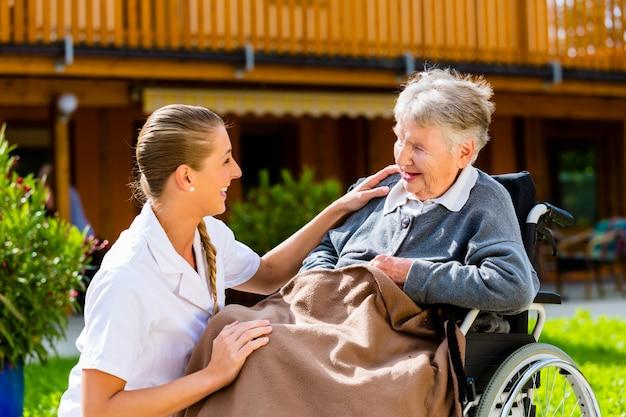 Verpleegster die hogere vrouw in rolstoel op gang duwt Premium Foto