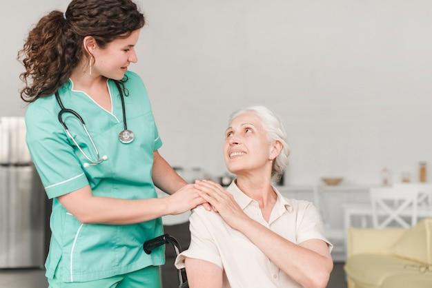 Verpleegster die hulp geeft aan gehandicapte vrouwelijke hogere geduldige zitting op rolstoel Gratis Foto