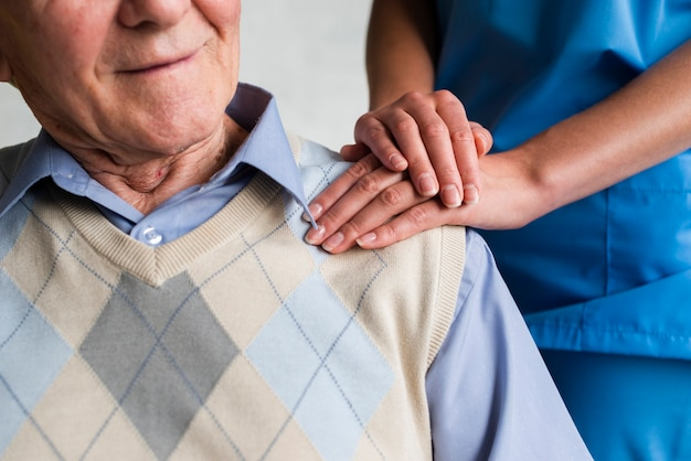 Verpleegster die oud man schouderclose-up houdt Premium Foto