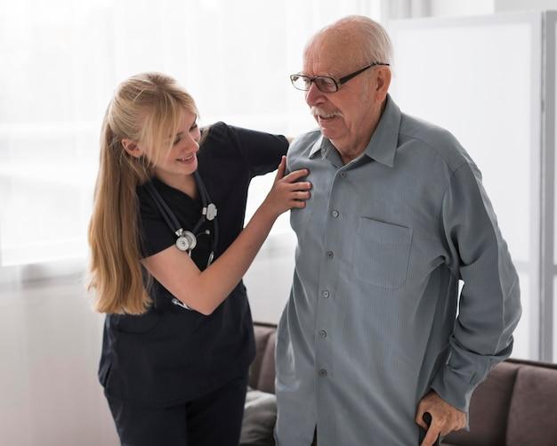 Verpleegster die oude man helpt opstaan Gratis Foto
