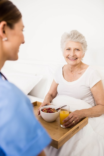 Verpleegster die thuis voor lijdende hogere patiënt zorgt Premium Foto