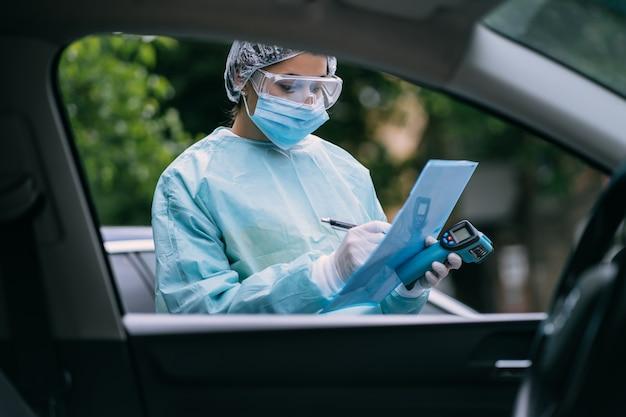 Verpleegster draagt een beschermend pak en masker tijdens de covid19-uitbraak. Gratis Foto