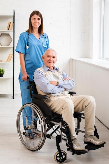 Verpleegster en oude man die zich voordeed tijdens het kijken naar de camera Gratis Foto