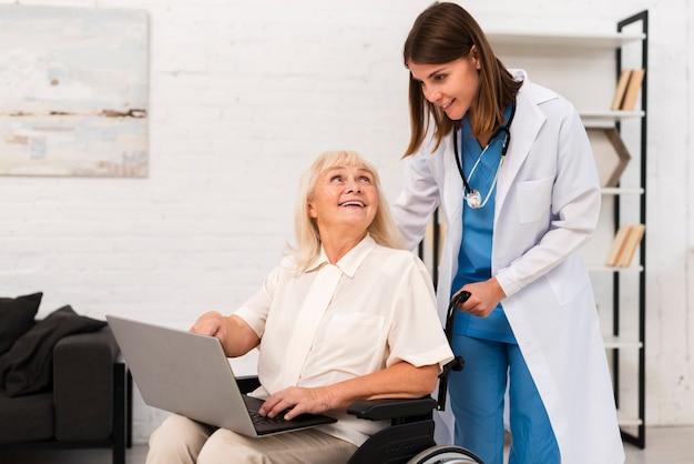 Verpleegster en oude vrouw die laptop controleren Gratis Foto