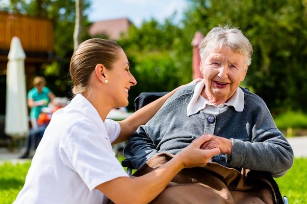 Verpleegster hand in hand met senior vrouw in rolstoel Premium Foto