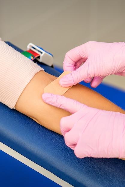 Verpleegster hand zelfklevende pleister toe te passen op de arm van de patiënt Premium Foto