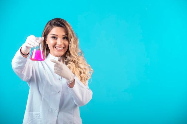 Verpleegster in wit uniform met een chemische kolf met roze vloeistof en voelt zich positief. Gratis Foto