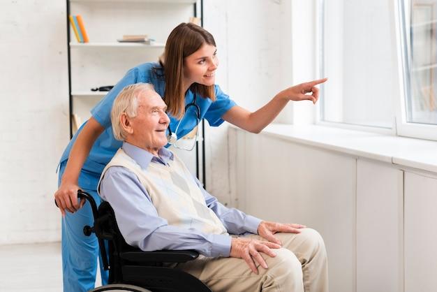 Verpleegster wijst naar het raam tijdens het praten met de oude man Premium Foto
