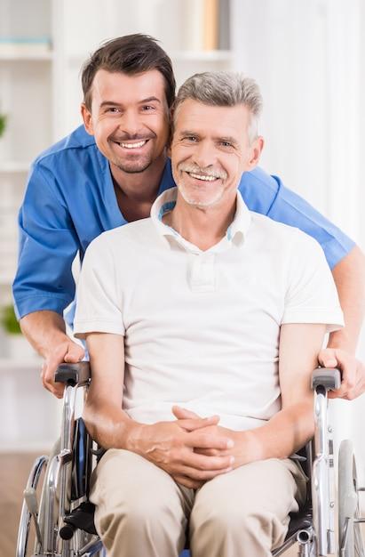 Verpleger die met hogere patiënt in rolstoel spreekt. Premium Foto