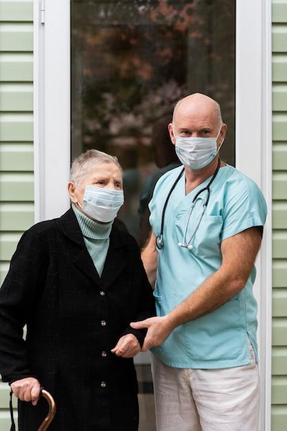 Verpleger en oudere vrouw met medische maskers Gratis Foto