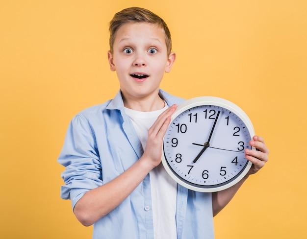 Verrassings glimlachende jongen die het witte klok in hand kijken aan camera tegen gele achtergrond houden Gratis Foto