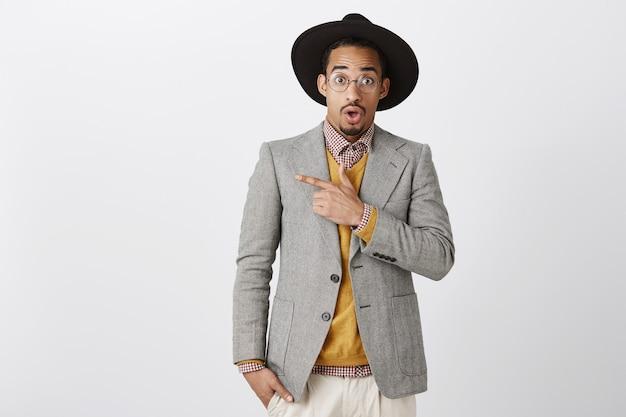 Verrast afro-amerikaanse man in pak vraag stellen en verbaasd linksboven Gratis Foto