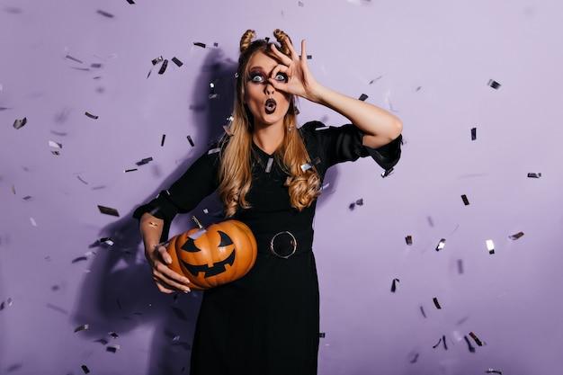 Verrast blonde heks die zich onder confetti bevindt. geschokt jonge vrouw poseren op paarse muur met halloween-pompoen. Gratis Foto