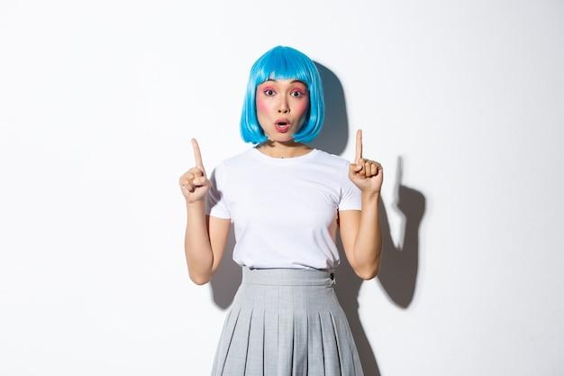 Verrast en gefascineerd aziatisch meisje in blauwe korte pruik, kawaii make-up, kijkt onder de indruk en wijst met de vingers omhoog, toont logo of promobanner, staand. Premium Foto