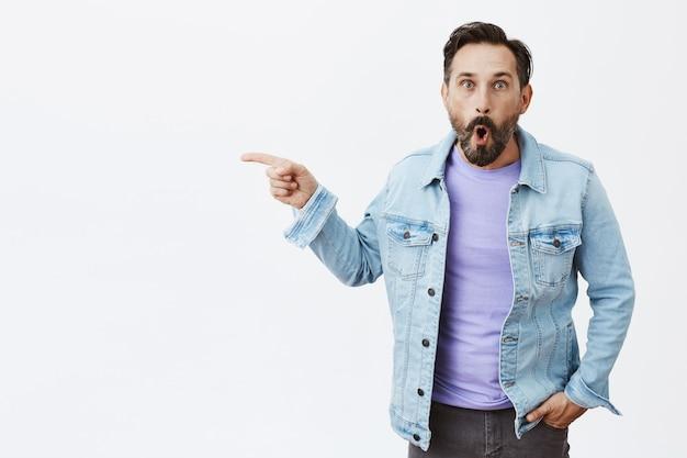 Verrast en gefascineerd bebaarde volwassen man poseren Gratis Foto