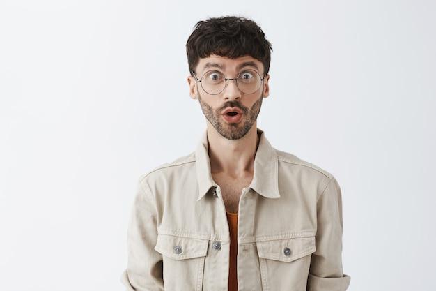 Verrast en gefascineerd stijlvolle bebaarde man poseren tegen de witte muur Gratis Foto