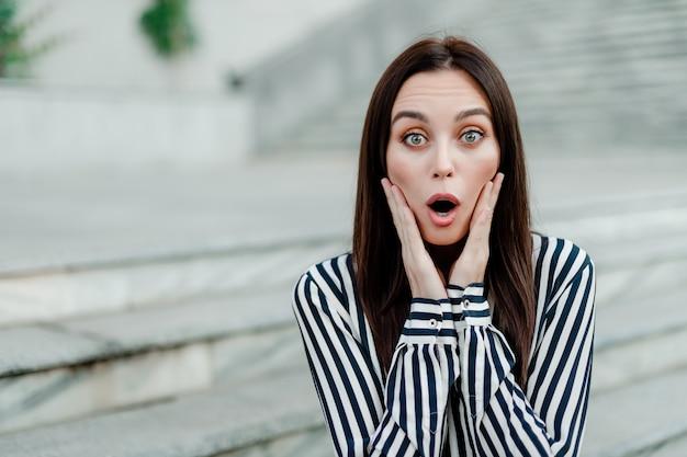 Verrast en geschokt vrouw buitenshuis Premium Foto