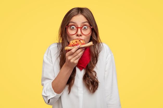 Verrast europese modieuze vrouw heeft stuk pizza, ziet er gekleed in een oversized shirt, verrast met een zeer goede smaak, geïsoleerd over gele muur. mensen en fastfood-concept Gratis Foto