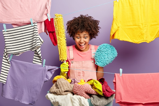 Verrast gelukkig afro-amerikaanse huisvrouw houdt dweil en borstel om stof af te vegen, staart naar kleine rubberen eend op stapel wasgoed achtergelaten door kind, doet huishoudelijke klusjes, bezig met wassen en schoonmaken. Gratis Foto