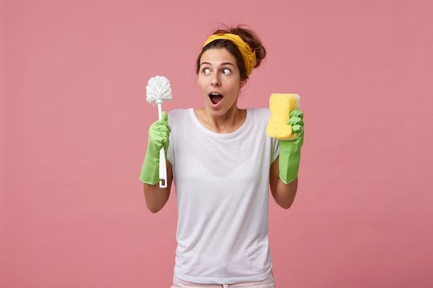 Verrast huisvrouw in casual wit t-shirt en beschermende handschoenen voor het schoonmaken gaat de kamer opruimen met borstel met spons met een verbaasde blik terwijl ze zich herinnert aan haar ontmoeting met vriend Gratis Foto