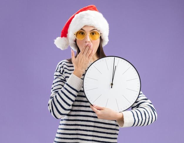 Verrast jong kaukasisch meisje in zonnebril met kerstmuts legt hand op mond en houdt klok Gratis Foto