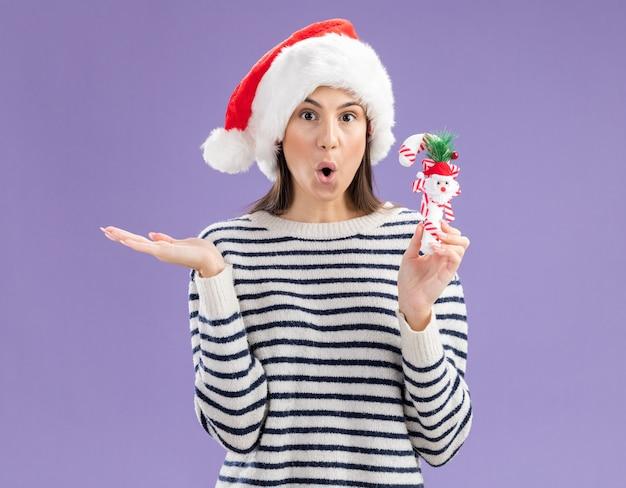 Verrast jong kaukasisch meisje met kerstmuts houdt snoepgoed en houdt de hand open Gratis Foto