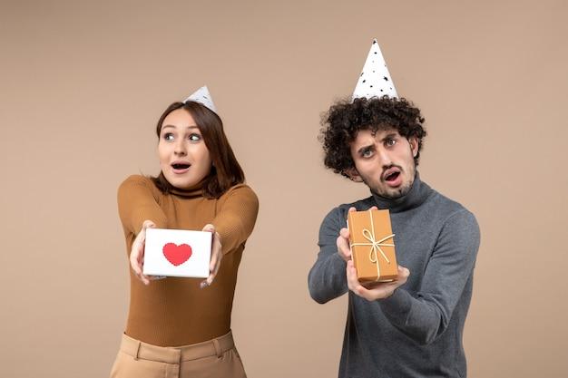 Verrast jong koppel dragen nieuwe jaar hoed vormt voor camera meisje met hart en man met cadeau op grijs Gratis Foto