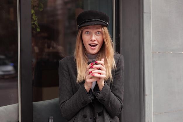 Verrast jonge mooie blonde vrouw in modieuze kleding ogen afronden tijdens het kijken, poseren over groot raam buiten met papieren beker in opgeheven handen Gratis Foto