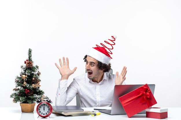 Verrast jonge zakenman met grappige kerstman hoed kerstboom versieren en kerstmis vieren in het kantoor op witte achtergrond Gratis Foto