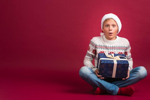 Verrast jongen met kerstcadeau Gratis Foto