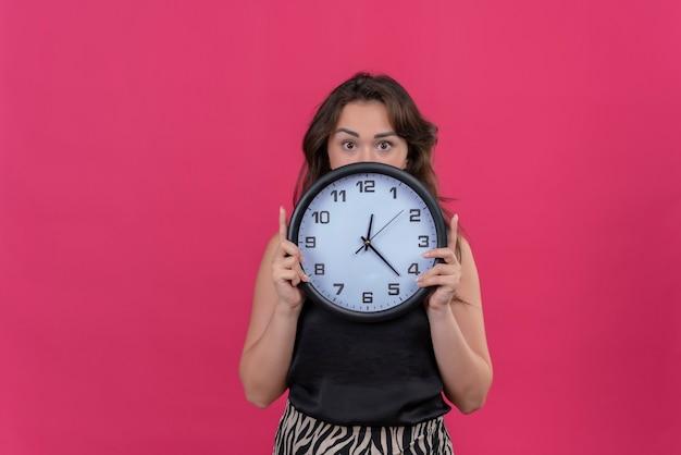 Verrast kaukasisch meisje dat een zwart onderhemd draagt dat een muurklok op roze achtergrond houdt Gratis Foto