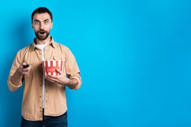 Verrast man met popcorn emmer en afstandsbediening Gratis Foto