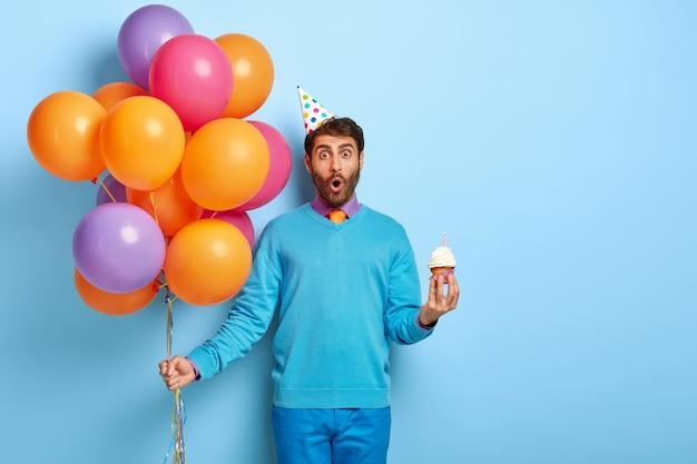 Verrast man met verjaardagshoed en ballonnen poseren in blauwe trui Gratis Foto