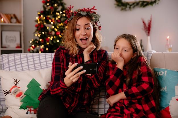 Verrast moeder en dochter kijken naar telefoon zittend op de bank en genieten van kersttijd thuis Gratis Foto