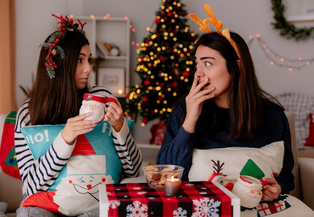 Verrast mooie jonge meisjes met hulstkrans en rendieren hoofdband houden kopjes kijken elkaar zittend op fauteuils en genieten van kersttijd thuis Gratis Foto