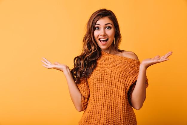 Verrast mooie vrouw poseren op helder geel. mooi donkerbruin meisje dat zich in studio met verbaasde gezichtsuitdrukking bevindt. Gratis Foto
