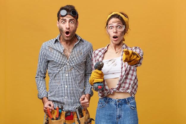 Verrast paar mannelijke en vrouwelijke elektrotechnici in veiligheidsbril en overall met verbaasde blikken, meisje met boor wijzende wijsvinger, iets schokkends tonen Gratis Foto