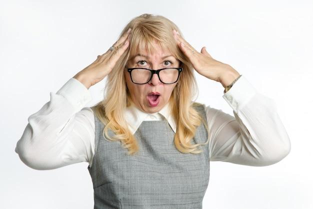 Verrast volwassen vrouw in glazen gebaren haar emoties op een lichte achtergrond. Premium Foto