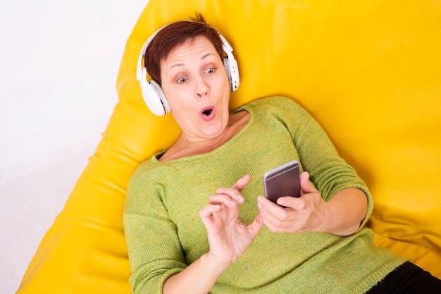 Verrast vrouw op bank luisteren muziek Gratis Foto