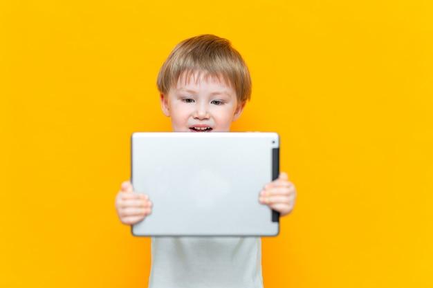 Verraste blonde drie jaar oude jongens met zijn open mond verrast, houdend in zijn handen een tabletpc en bekijkend de camera Premium Foto