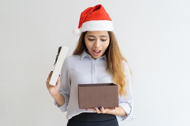 Verraste dame die de hoed van de kerstman draagt en in giftdoos piept Gratis Foto