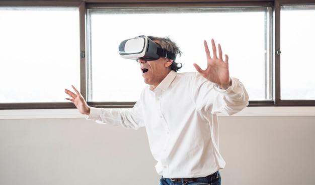 Verraste hogere mens die een virtuele werkelijkheidshoofdtelefoon in de ruimte met behulp van Gratis Foto