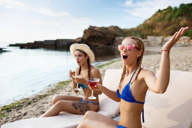 Verraste jonge mooie vrouwen die op chaises dichtbij overzees liggen Gratis Foto