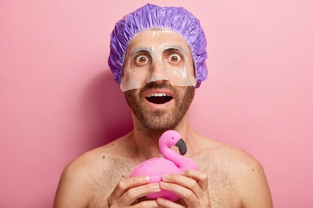 Verraste jongeman past cosmetisch masker toe, houdt badspons vast in de vorm van flamingo, draagt douchemuts, heeft hygiëneroutine, staat met blote romp Gratis Foto