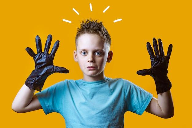 Verraste jongen in zwarte handschoenen en blauwe t-shirt op een gele achtergrond Premium Foto