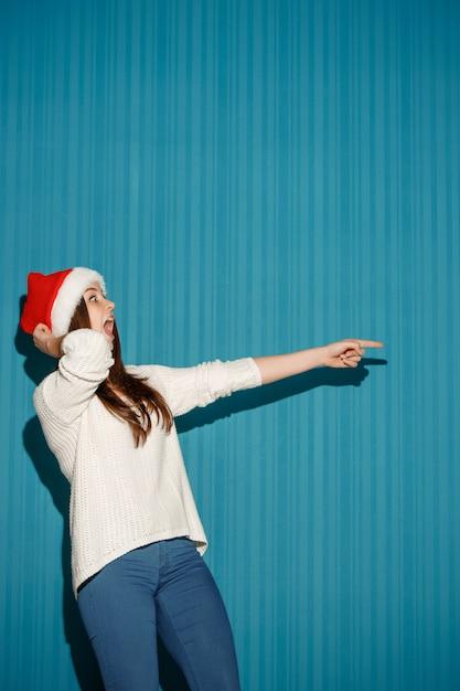 Verraste kerstmisvrouw die een santahoed draagt Gratis Foto